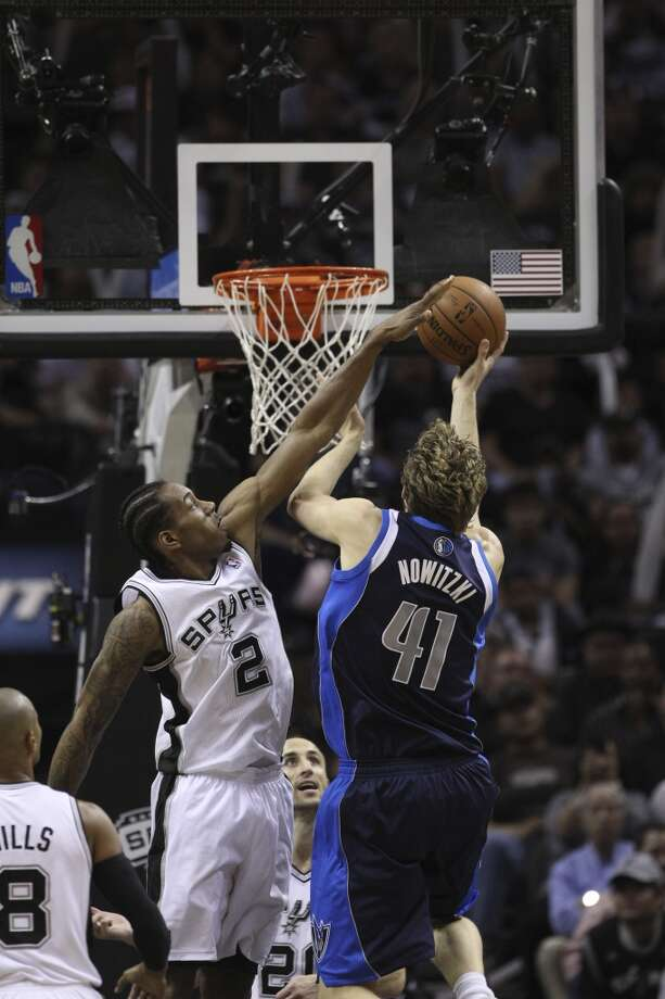 Spurs' Kawhi Leonard (02) reaches up to attempt a block on a shot by Dallas Mavericks' Dirk Nowitzki (41) in the second half of Game 5 of the first round of the Western Conference playoffs at the AT&T Center on Wednesday, Apr. 30, 2014. Spurs defeated the Mavericks, 109-103. (Kin Man Hui/San Antonio Express-News) Photo: San Antonio Express-News