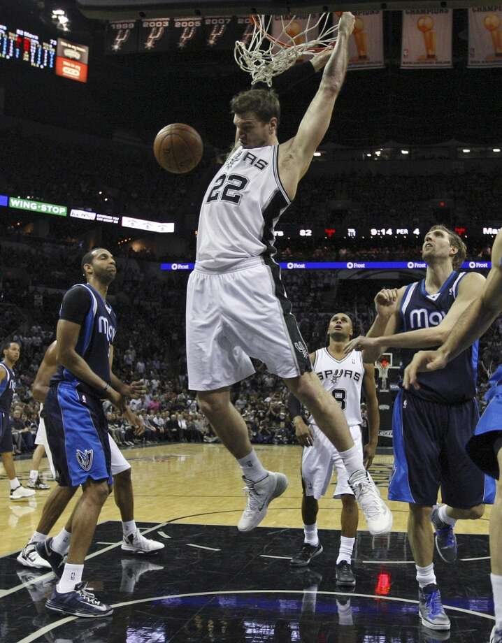 San Antonio Spurs' Tiago Splitter dunks the ball as Dallas Mavericks Brandan Wright, left, and Dirk Nowitzki look on during the second half of game five in the first round of the Western Conference Playoffs against the Dallas Mavericks at the AT&T Center, Wednesday, April 30, 2014. The Spurs won 109-103 to lead the series, 3-2. Photo: San Antonio Express-News