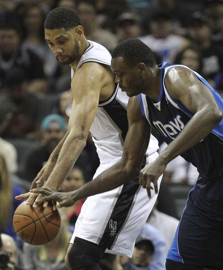 San Antonio Spurs' Tim Duncan and Dallas Mavericks' Samuel Dalembert goes for a loose ball during the first half of game five in the first round of the Western Conference Playoffs at the AT&T Center, Wednesday, April 30, 2014. Photo: San Antonio Express-News