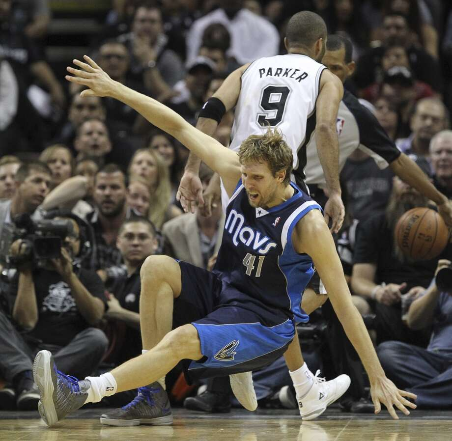 Dallas Mavericks' Dirk Nowitzki falls into San Antonio Spurs' Tony Parker during the first half of game five in the first round of the Western Conference Playoffs at the AT&T Center, Wednesday, April 30, 2014. Photo: San Antonio Express-News