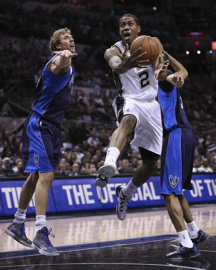 San Antonio Spurs' Kawhi Leonard hits the paint a Dallas Mavericks' Dirk Nowitzki defends during the first half of game five in the first round of the Western Conference Playoffs at the AT&T Center, Wednesday, April 30, 2014. Photo: San Antonio Express-News