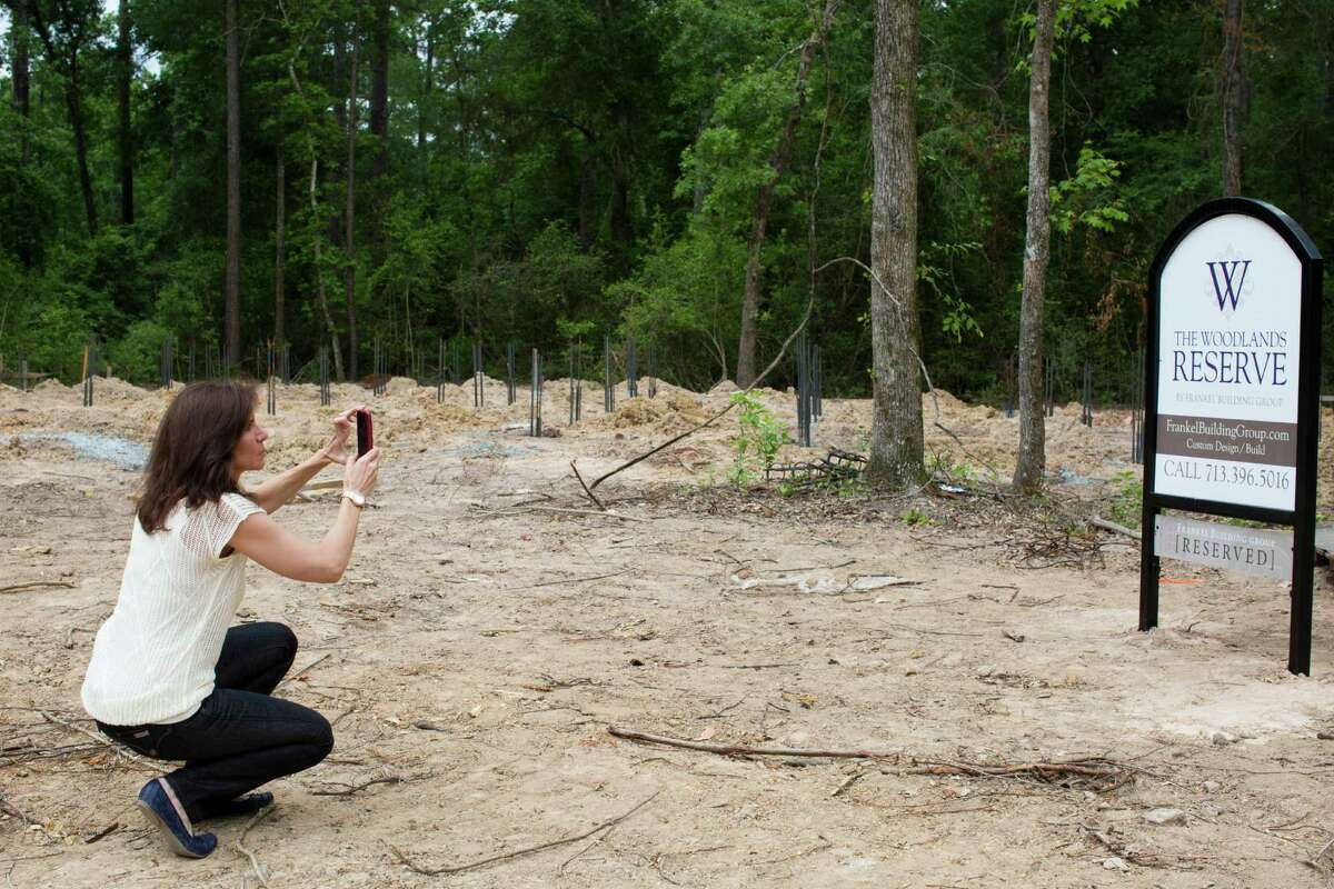 Lynn Fanelli takes a photo of the reserved sign on a lot where her home is being built. Fanelli and her husband, Mark Fanelli, decided to construct a house to their own specifications in The Woodlands Reserve.