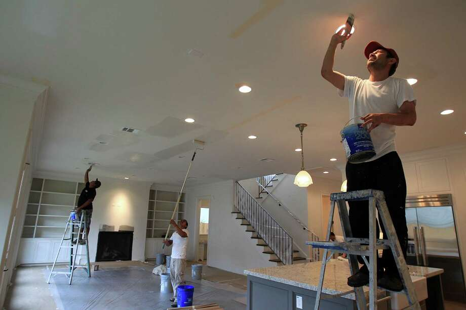 Adolfo Guerra, right, and other painters work in the kitchen and living room area in a Horace Homes built in the West University area on April 21, 2014, in Houston, Tx. The design trend is that homebuyers want a large, open kitchen and family room. ( Mayra Beltran / Houston Chronicle ) Photo: Mayra Beltran, Staff / © 2014 Houston Chronicle