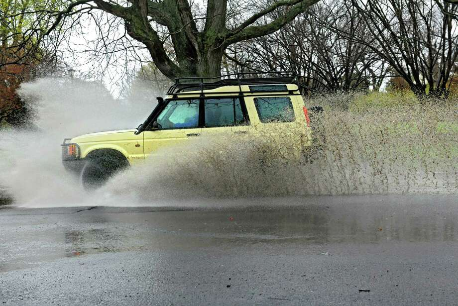 An SUV drives through a deep puddle in Washington Park Wednesday, April 30, 2014, in Albany, N.Y  (Lori Van Buren / Times Union) Photo: Lori Van Buren