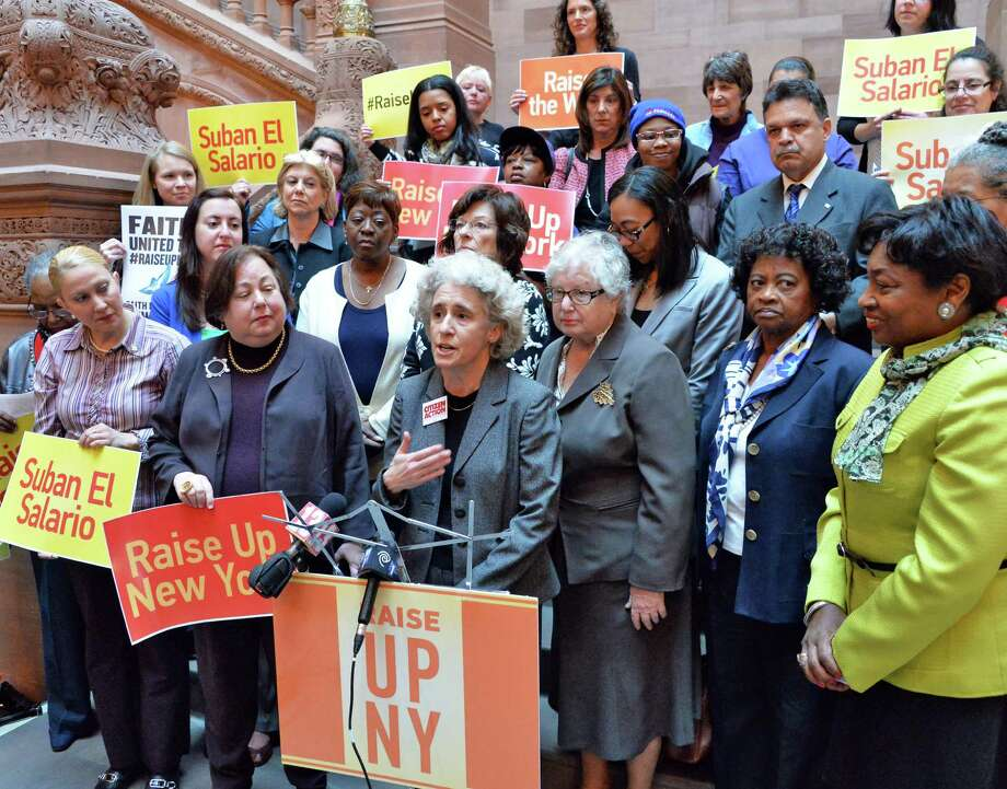 Karen Scharff, center, of Citizens Action of New York joins a group of prominent women leaders to demand support for legislation allowing cities and counties to raise wages above the state's minimum wage Wednesday April 30, 2014, during a demonstration at the Capitol in Albany, N.Y.  (John Carl D'Annibale / Times Union) Photo: John Carl D'Annibale / 00026693A