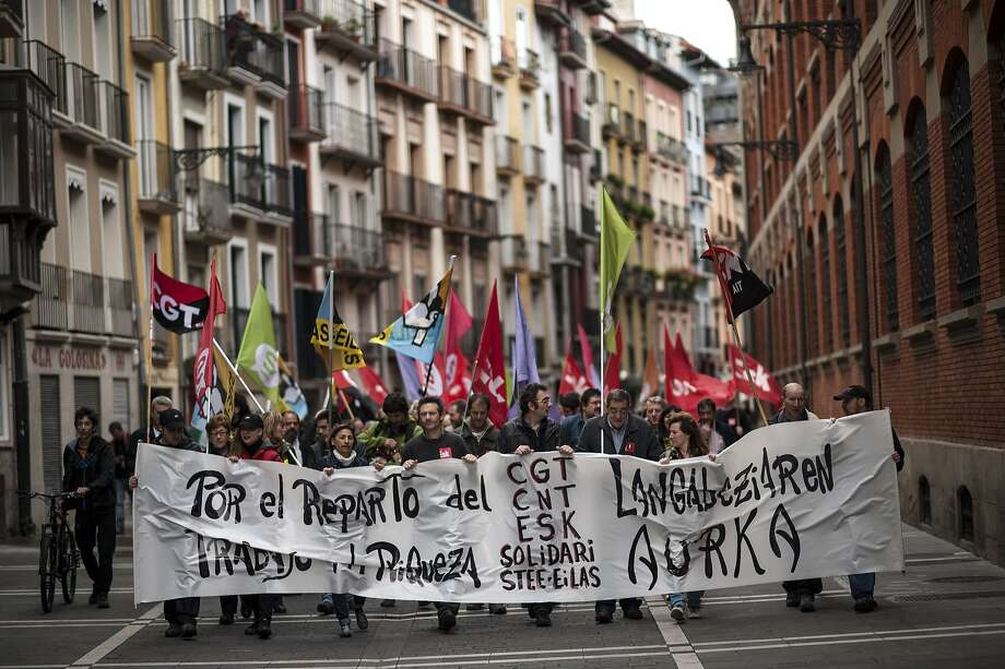 Workers march on the street holding a banner which reads:  ''For the distribution the work and wealth'', during May Day, in Pamplona northern Spain, Thursday, May 1, 2014. Tens of thousands of workers marked May Day in European cities with a mix of anger and gloom over austerity measures imposed by leaders trying to contain the eurozone's intractable debt crisis. Photo: Alvaro Barrientos, Associated Press