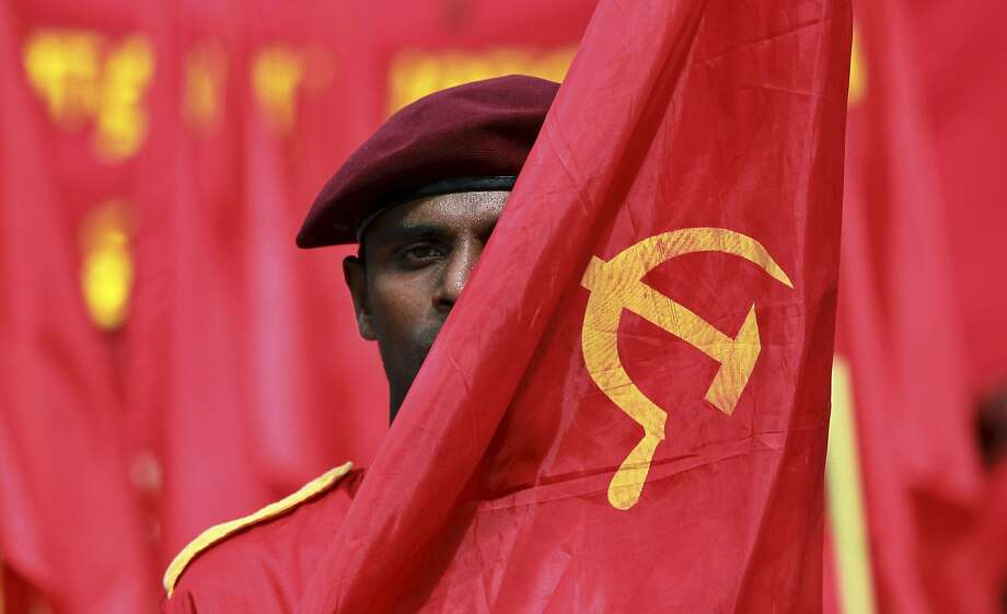 A member of Sri Lanka's Marxist Party Peoples Liberation Front carries a flag symbolizing the working class during a parade held to mark the International Labor Day or May Day in Colombo, Sri Lanka, Thursday, May 1, 2014. Photo: Eranga Jayawardena, Associated Press