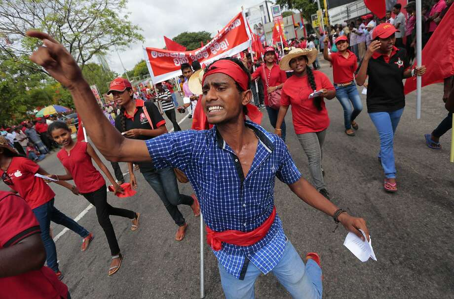 A member of Sri Lanka's Marxist Party Peoples Liberation Front shouts slogans against the Sri Lankan government during a parade held to mark the International Labor Day or May Day in Colombo, Sri Lanka, Thursday, May 1, 2014. Photo: Eranga Jayawardena, Associated Press