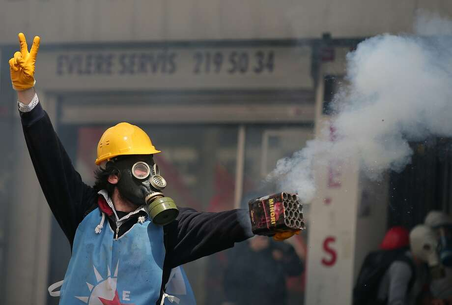 A protester stands as riot police use water cannons and teargas to disperse thousands of people trying to reach the city's main Taksim Square to celebrate May Day in Istanbul, Turkey, Thursday, May 1, 2014. Clashes erupted between May Day demonstrators and riot police as crowds determined to defy a government ban tried to march to the city's iconic Taksim Square. Security forces pushed back demonstrators with water cannons and tear gas. Photo: Emrah Gurel, Associated Press