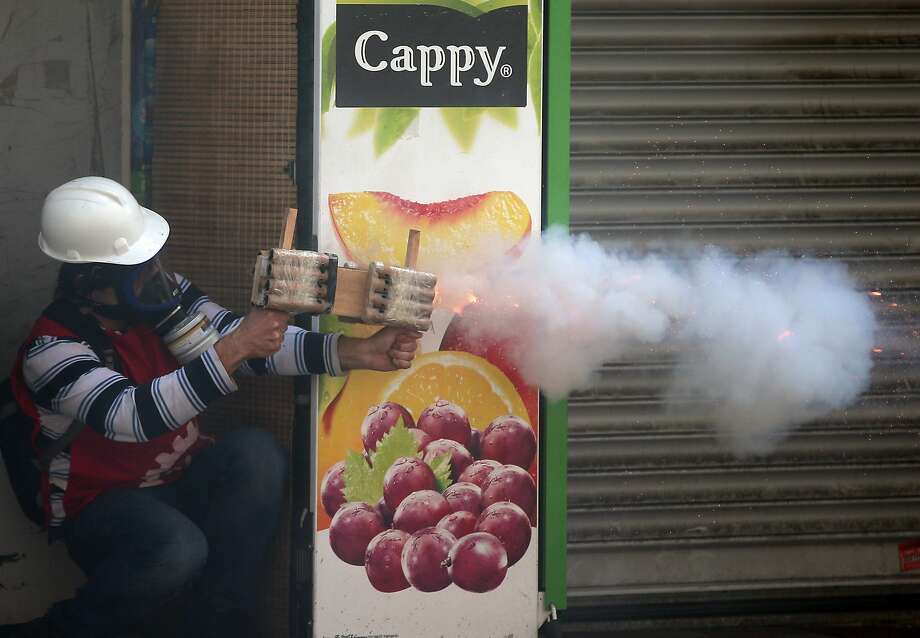 A protester fires toward riot police in Istanbul, Turkey, Thursday May 1, 2014. Clashes erupted between May Day demonstrators and riot police as crowds determined to defy a government ban tried to march to the city's iconic Taksim Square. Security forces pushed back demonstrators with water cannons and tear gas. Photo: Emrah Gurel, Associated Press
