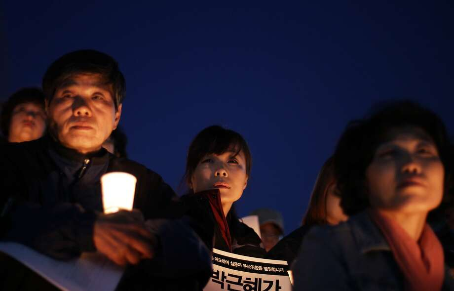 People hold candles as they pray for the safe return of missing passengers and  tribute to the victims of the sunken ferry Sewol on May 1, 2014 in Seoul, South Korea. No survivors have been found since 174 passengers and crew were rescued on the day of the incident, April 16. South Korea's trade union, the Federation of Korean Trade Unions (FKTU) had announced cancellation of its annual May Day rally to mourn the ferry disaster victims.  Photo: Chung Sung-Jun, Getty Images