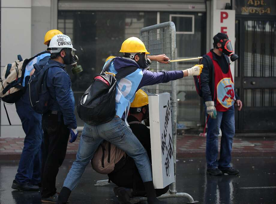 A protester uses a slingshot toward riot police in Istanbul, Turkey, Thursday May 1, 2014. Clashes erupted between May Day demonstrators and riot police as crowds determined to defy a government ban tried to march to the city's iconic Taksim Square. Security forces pushed back demonstrators with water cannons and tear gas. Photo: Emrah Gurel, Associated Press
