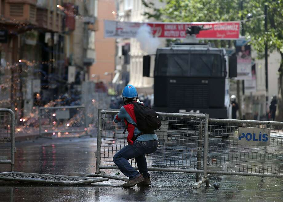 A protester uses a slingshot toward riot police who use water cannons and teargas to disperse thousands of people trying to reach the city's main Taksim Square to celebrate May Day in Istanbul, Turkey, Thursday, May 1, 2014. Clashes erupted between May Day demonstrators and riot police as crowds determined to defy a government ban tried to march to the city's iconic Taksim Square. Security forces pushed back demonstrators with water cannons and tear gas. Photo: Emrah Gurel, Associated Press