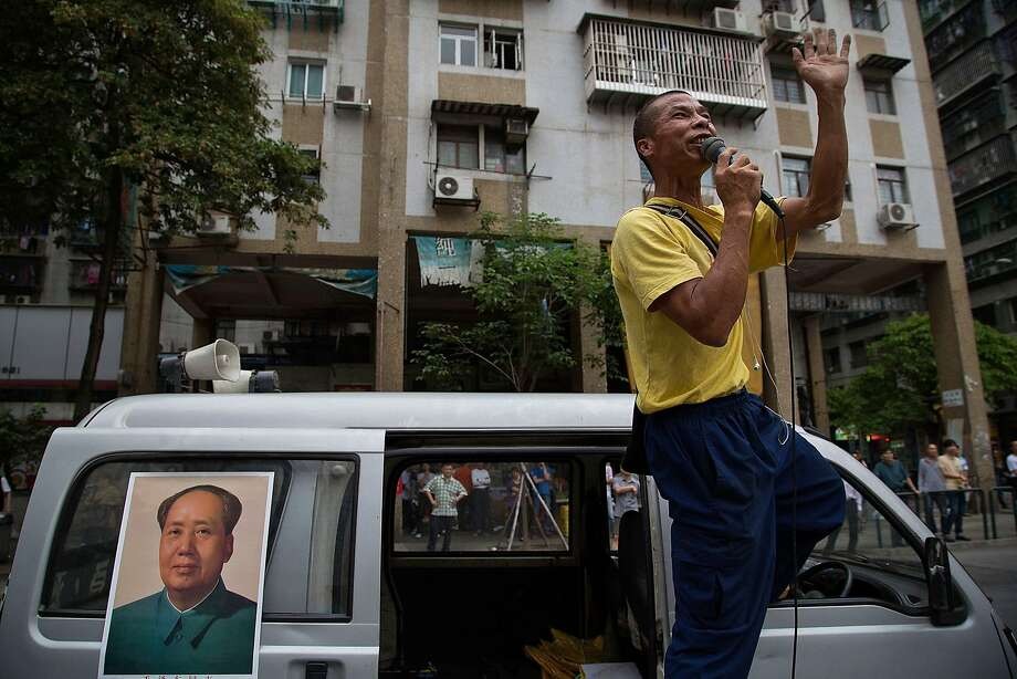 A protester shouts slogans as he stands on top of a van during a May Day demonstration on May 1, 2014 in Macau, China. Hundreds of protesters attended a march against job shortages and living conditions on May Day.  Photo: Lam Yik Fei, Getty Images