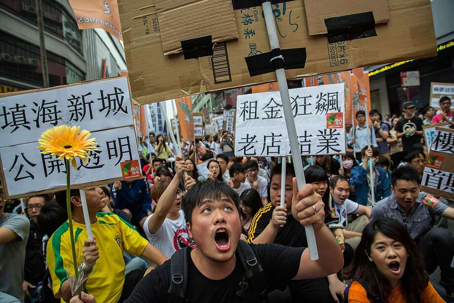 Protesters shout slogans and hold banners during a May Day demonstration on May 1, 2014 in Macau, China. Hundreds of protesters attended a march against job shortages and living conditions on May Day. Photo: Lam Yik Fei, Getty Images