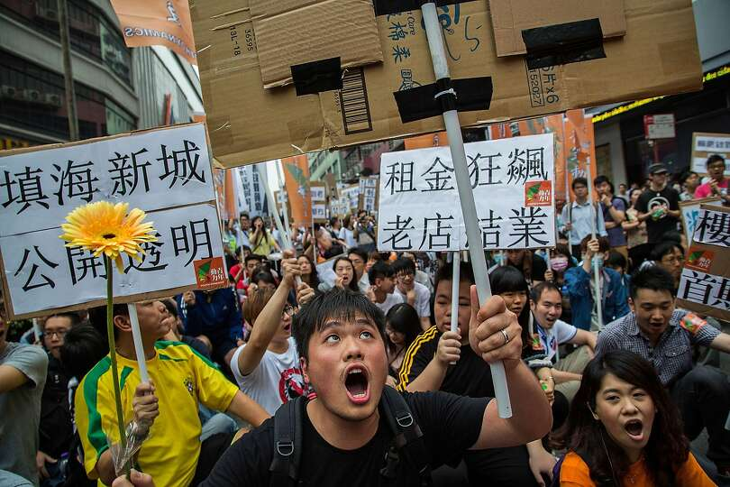 Protesters shout slogans and hold banners during a May Day demonstration on May 1, 2014 in Macau, Ch