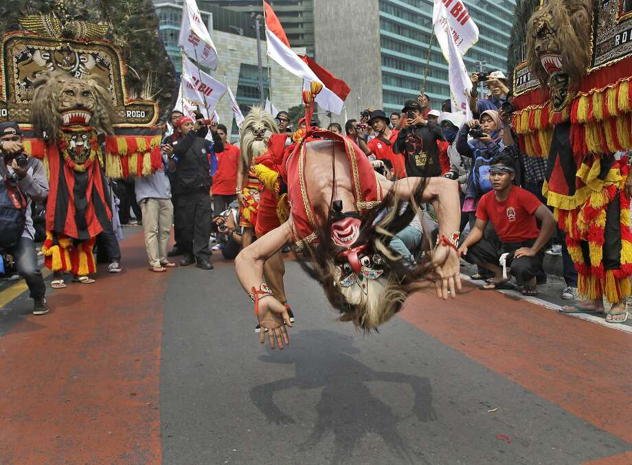 A masked dancer somersaults as he performs during a May Day rally in Jakarta, Indonesia, Thursday, May 1, 2014. Photo: Dita Alangkara, Associated Press