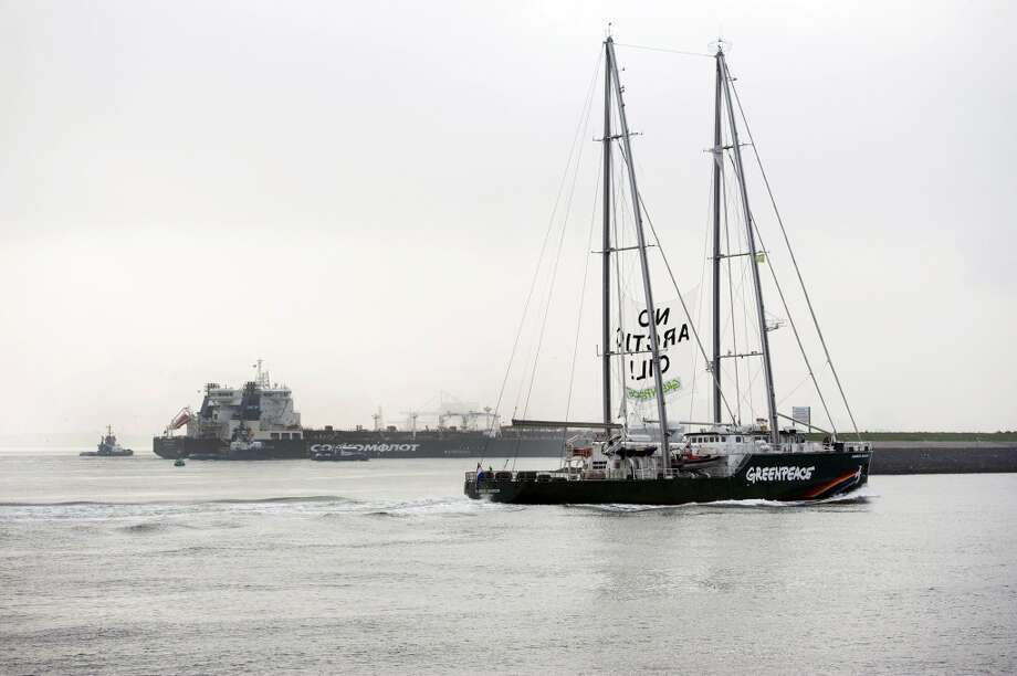 The Greenpeace ship Rainbow Warrior showing a banner reading: 'No Arctic Oil' as Greenpeace activists aboard inflatable boats paint 'No Arctic Oil' on the side of the Mikhail Ulyanov oil tanker, seen in the background, in Rotterdam, Netherlands, on Thursday, May 1, 2014. Greenpeace International activists are attempting to prevent a Russian tanker carrying the first oil from a new offshore platform in the Arctic from mooring at Rotterdam Port. The environmental group said Thursday it has sent two ships, Rainbow Warrior III and Esperanza, plus rubber rafts, paragliders and activists on shore, to meet the Mikhail Ulyanov, a tanker chartered by Russia's state-controlled oil company, Gazprom OAO. (AP Photo/Marten van Dijl, Greenpeace) NO SALES, NO ARCHIVE Photo: Marten  Van Dijl, ASSOCIATED PRESS