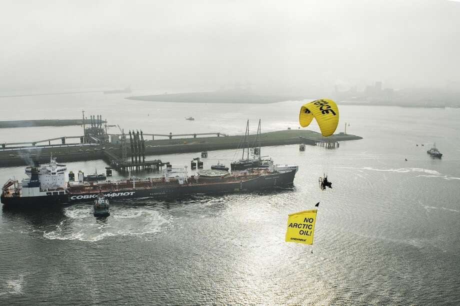 Greenpeace shows the Greenpeace ship Esperanza, paragliders and Greenpeace inflatable boats protest near the Mikhail Ulyanov oil tanker in the harbor of Rotterdam, Netherlands, on Thursday, May 1, 2014. Greenpeace International activists are attempting to prevent a Russian tanker carrying the first oil from a new offshore platform in the Arctic from mooring at Rotterdam Port. The environmental group said Thursday it has sent two ships, Rainbow Warrior III and Esperanza, plus rubber rafts, paragliders and activists on shore, to meet the Mikhail Ulyanov, a tanker chartered by Russia's state-controlled oil company, Gazprom OAO. Photo: Ruben Neugebauer, ASSOCIATED PRESS