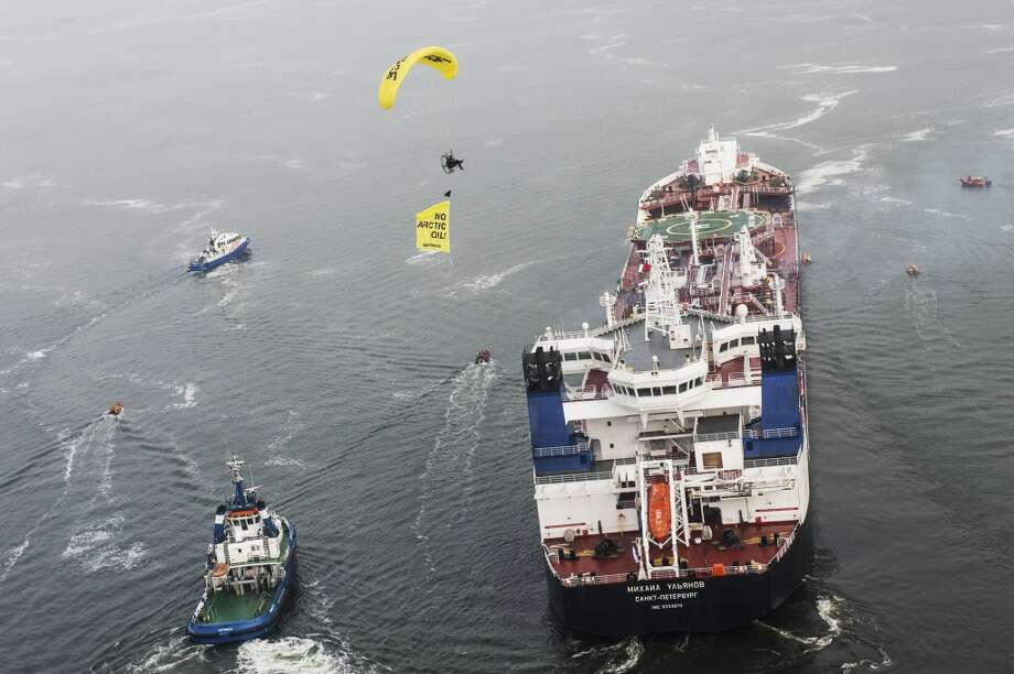 Greenpeace ship Esperanza, paragliders and Greenpeace inflatable boats protest near the Mikhail Ulyanov oil tanker, left, in the harbor of Rotterdam, Netherlands, on Thursday, May 1, 2014. Greenpeace International activists are attempting to prevent a Russian tanker carrying the first oil from a new offshore platform in the Arctic from mooring at Rotterdam Port. The environmental group said Thursday it has sent two ships, Rainbow Warrior III and Esperanza, plus rubber rafts, paragliders and activists on shore, to meet the Mikhail Ulyanov, a tanker chartered by Russia's state-controlled oil company, Gazprom OAO. Photo: Ruben Neugebauer, AP