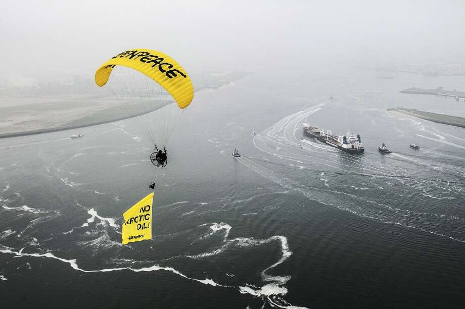 Greenpeace ship Esperanza, paragliders and Greenpeace inflatable boats protest near the Mikhail Ulyanov oil tanker, right, in the harbor of Rotterdam, Netherlands, on Thursday, May 1, 2014. Greenpeace International activists are attempting to prevent a Russian tanker carrying the first oil from a new offshore platform in the Arctic from mooring at Rotterdam Port. The environmental group said Thursday it has sent two ships, Rainbow Warrior III and Esperanza, plus rubber rafts, paragliders and activists on shore, to meet the Mikhail Ulyanov, a tanker chartered by Russia's state-controlled oil company, Gazprom OAO. Photo: Ruben Neugebauer, AP