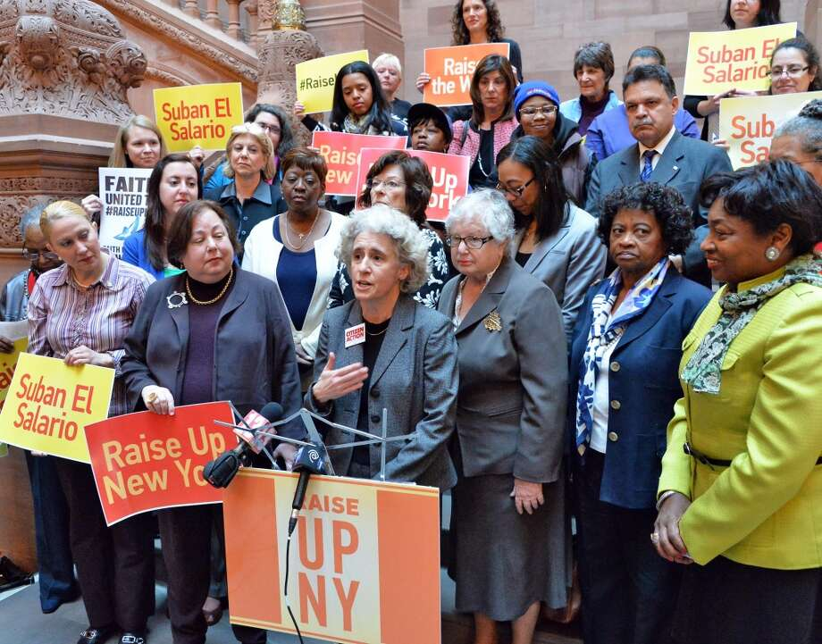 Karen Scharff, center, of Citizens Action of New York joins a group of prominent women leaders to demand support for legislation allowing cities and counties to raise wages above the state's minimum wage Wednesday April 30, 2014, during a demonstration at the Capitol in Albany, N.Y.  (John Carl D'Annibale / Times Union) Photo: John Carl D'Annibale, Albany Times Union
