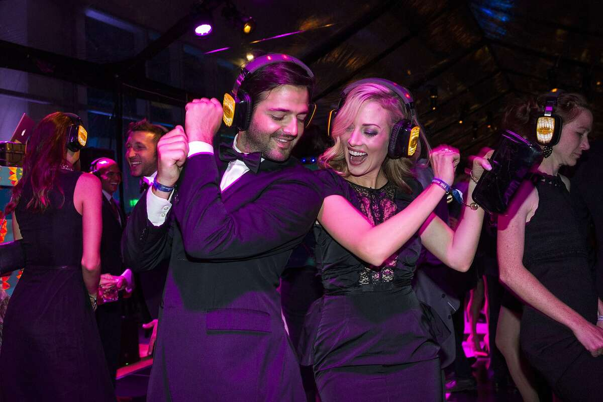 Noah Lichtenstein and Tiffany Lyon dance to the silent disco while attending the Post-Modern Party, part of SFMOMA's Modern Ball, at City View at Metreon in San Francisco, Calif., on Wednesday, April 30 2014.