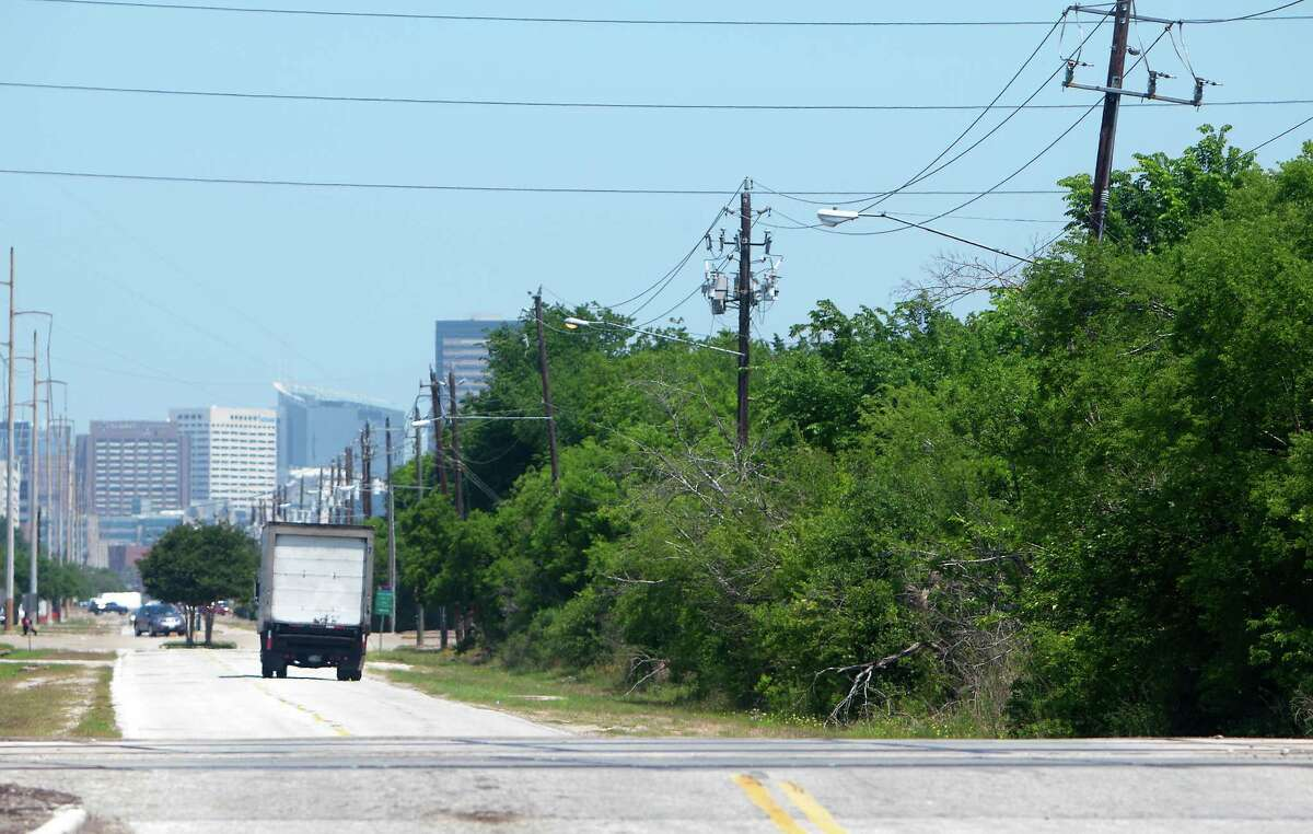 The Texas Medical Center is seen in the distance as trees line Knight Road near Holmes Road, Friday, April 25, 2014, in Houston. The area currently lacks a sewer line pushing developers elsewhere with lower up front costs. Houston and Harris County officials propose to fix that by burying an $11 million sewer pipe along Holmes Road and make 1,400 acres ready for development.