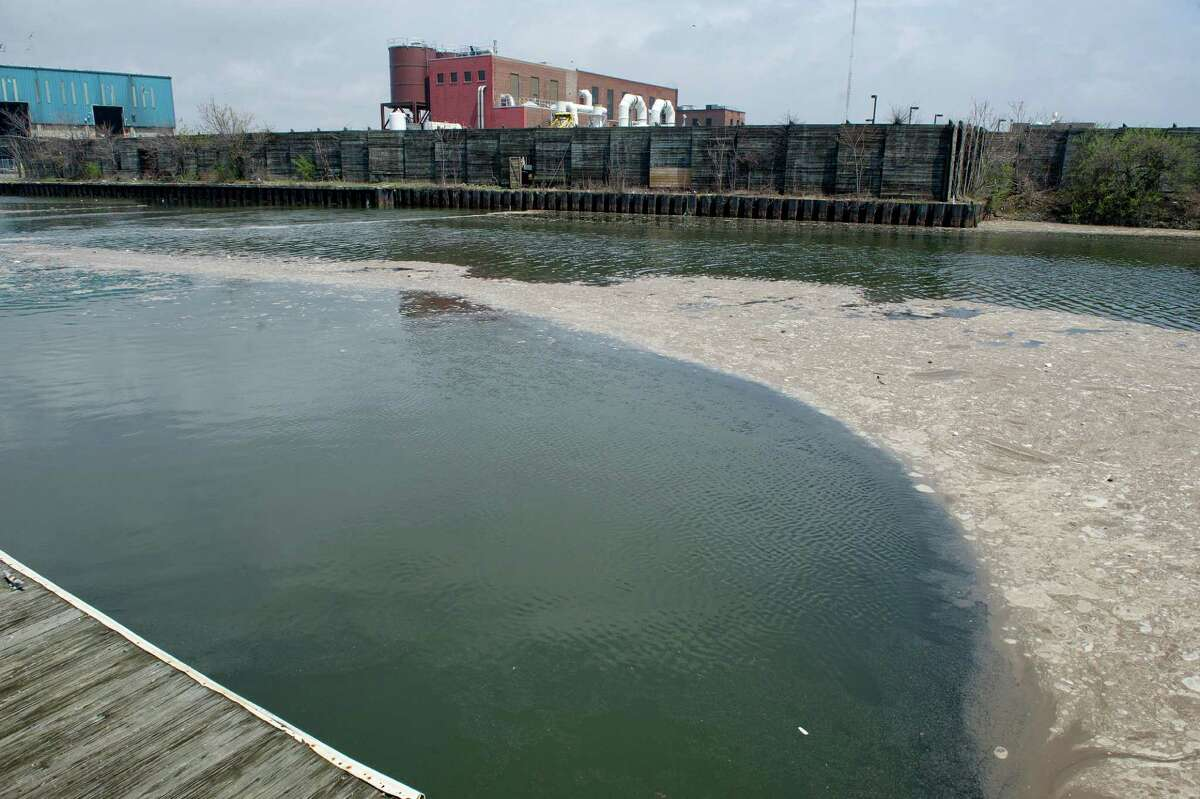 Sewage from the Wastewater Pollution Control Authority, which is visible in the background, floats in the water of Stamford Harbor in Stamford, Conn., on Thursday, May 1, 2014.