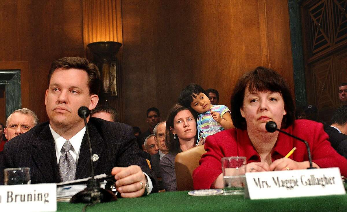 Margaret Conway, center background, of Washington and her daughter Quinn watch in the audience on Capitol Hill Wednesday, March 3, 2004, as the Senate Judiciary Constitution, Civil Rights and Property Subcommittee, begins hearings on judicial invalidation of traditional marriage laws. Nebraska Attorney General Jon Bruning and Maggie Gallagher, president of the Institute for Marriage and Public Policy, wait to testify in the foreground. (AP Photo/Dennis Cook)