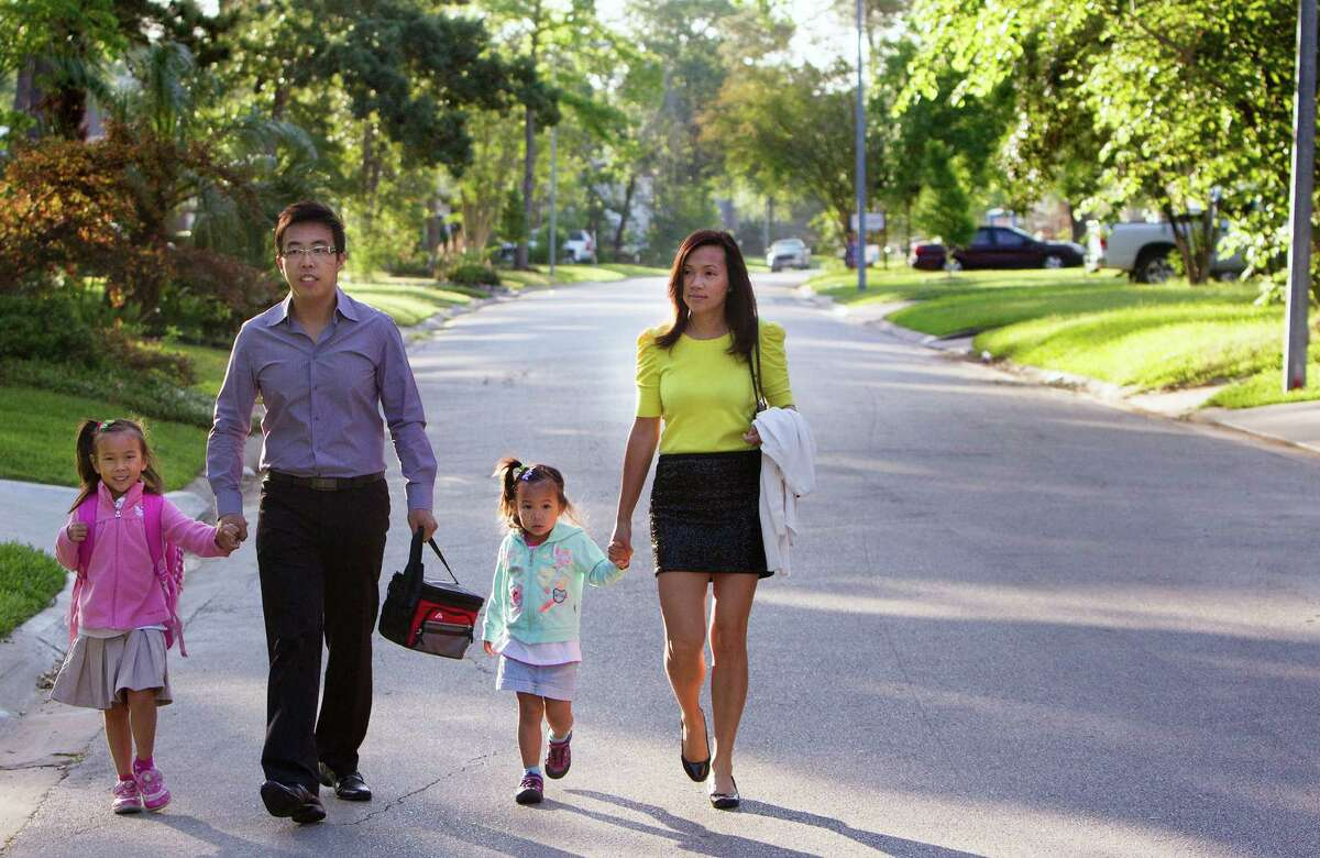From left, Meadow Lam, 6, her father, Herman Lam, her sister, Autumn Lam, 3, and mother, Carrie Lam, walk her to her Oak Forest Elementary School, Thursday, May 1, 2014, in Houston. The Lams decided to move to Oak Forest after touring the school and they like being able to walk their daughter there. (Cody Duty / Houston Chronicle)