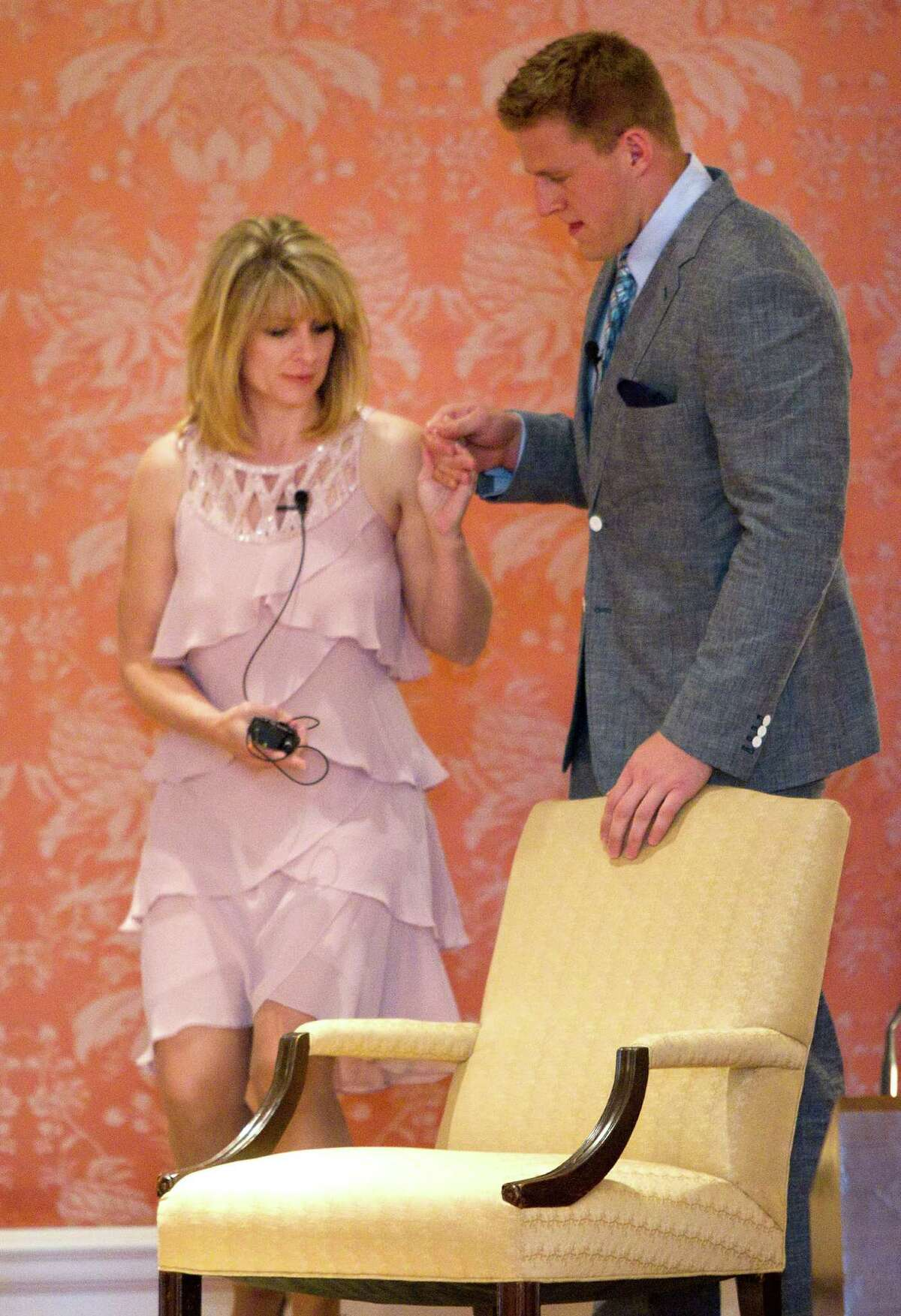 Houston Texans defensive end J.J. Watt helps his mom, Connie, to the stage as the mother and son are honored during a charity luncheon for Pro Vision Charter School Thursday, May 1, 2014, in Houston.