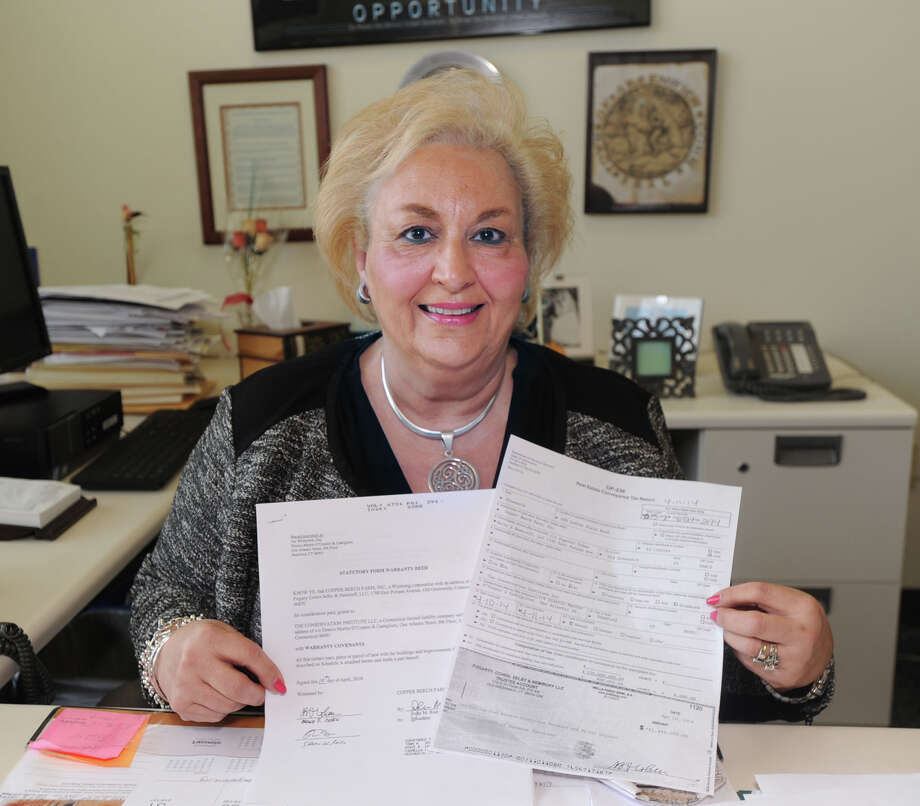 Greenwich Town Clerk, Carmella Budkins, with a conveyance tax check and deed documents from the recent sale of Copper Beech Farm for a record $120 million, at her office in Greenwich Town Hall, Thursday, May 1, 2014. Photo: Bob Luckey / Greenwich Time