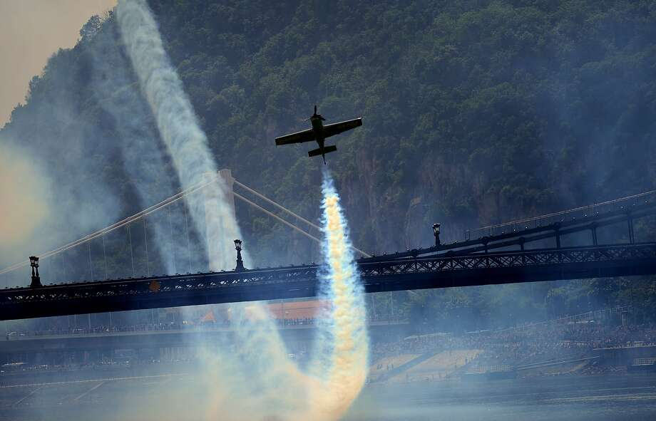 """Here he goes loop de loop:European champion pilot Zoltan Veres pulls up after a steep dive under the oldest Hungarian   bridge, the Lanchid (Chain Bridge), in Budapest. Veres performed stunts with his """"MXS""""-type plane during a Red Bull flying   show over the Danube River. Photo: Attila Kisbenedek, AFP/Getty Images"""
