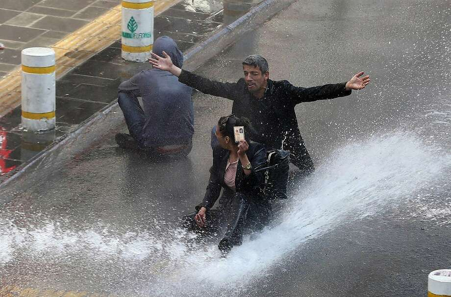 But I have ID: A protester holds up her identification card as riot police drench her and her companion with a water cannon during May Day clashes in Ankara. Photo: Adem Altan, AFP/Getty Images