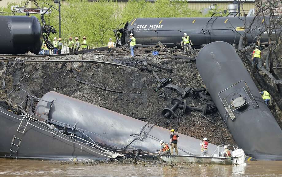 Crews work on cleanup at the site where several CSX tanker cars carrying crude oil derailed and caught fire along the James River near downtown Lynchburg, Va. The crash prompted an evacuation of the area. Photo: Steve Helber, Associated Press