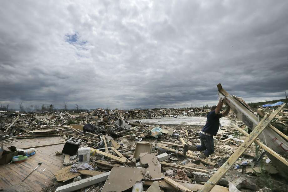 A neighborhood flattened: Dustin Shaw lifts debris as he searches through what is left of his sister's house 