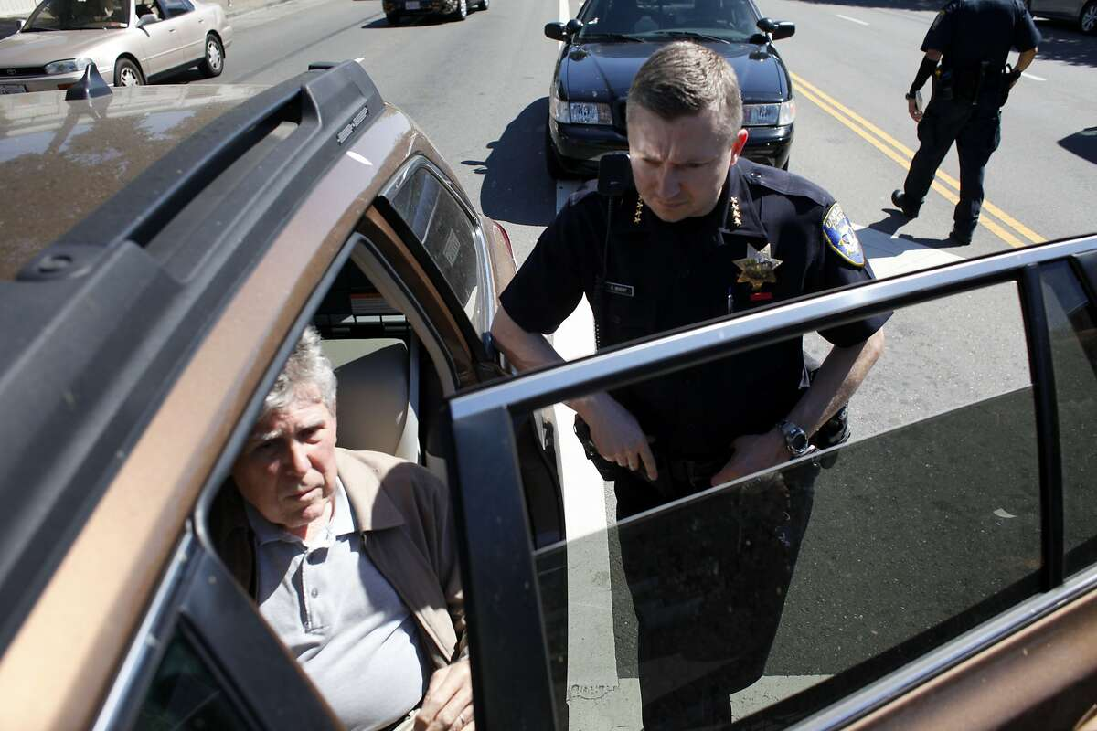 Oakland's new Police Chief Sean Whent, right checks on the passengers that were involved in a car accident, Monday May 13, 2013 on Telegraph Ave in Oakland, Calif.
