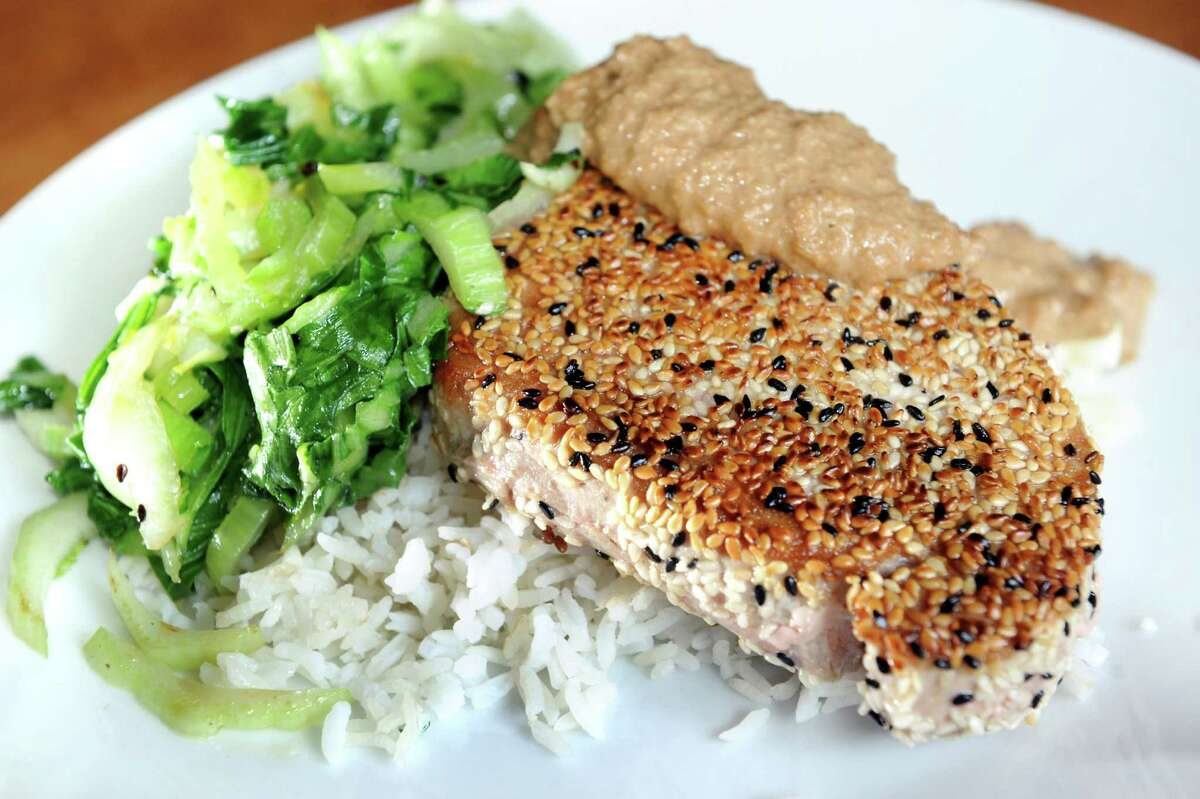 Seared Ahi Tuna Steak, black and white sesame seed encrusted with baby bok choy and a peanut satay over jasmine rice on Wednesday, April 23, 2014, at The Capital American Eatery and Lounge in Albany, N.Y. (Cindy Schultz / Times Union)