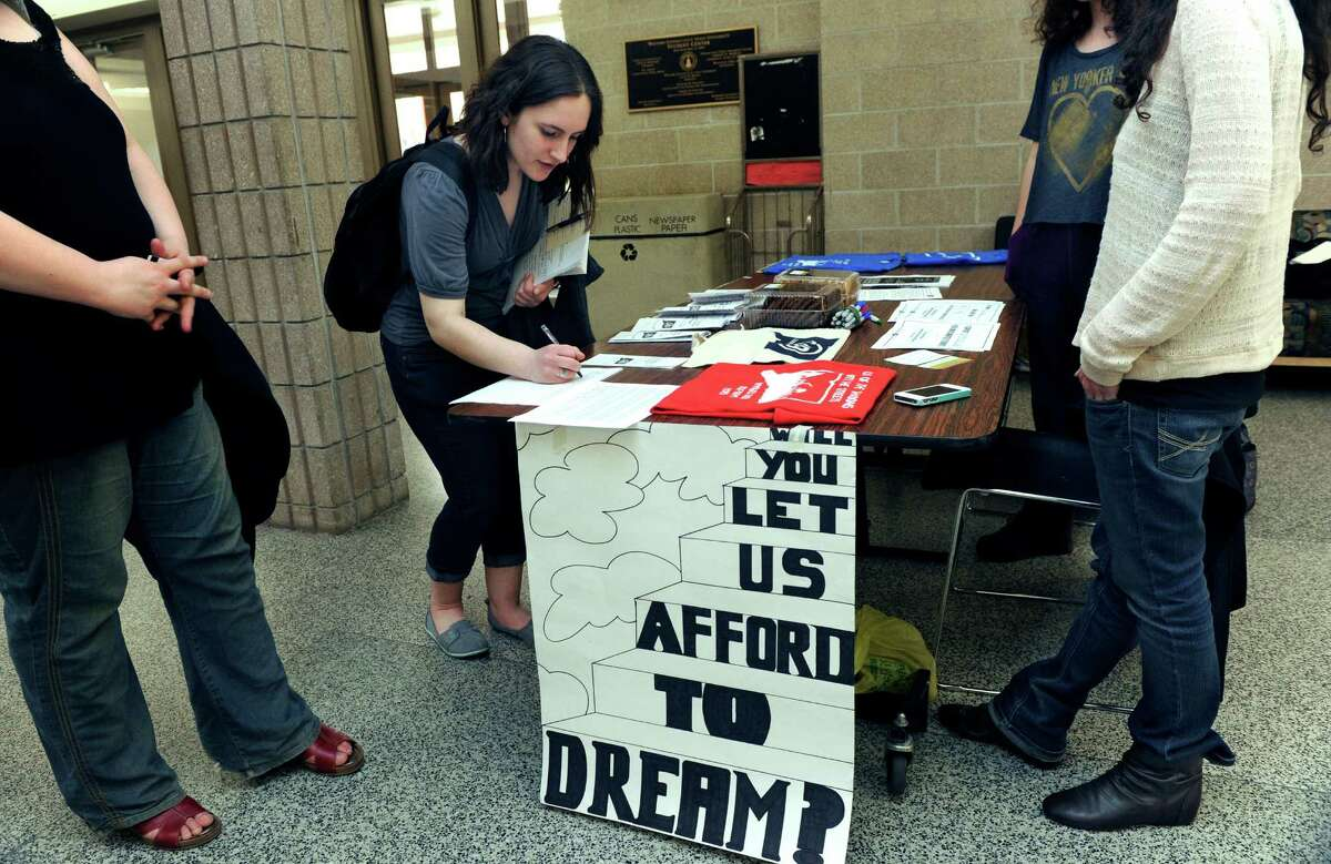 Brianna Halek, 24, of Brookfield, Conn., a senior at Western Connecticut State University, signs a petition Thursday, May 1, 2014. Connecticut Students for a DREAM want Connecticut to allow undocumented students to be eligible to recive scholarships that are funded by their tuition money.