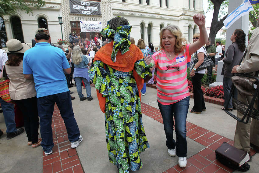 Connie Sowards, right, dances with Francisca McNair in front of City Hall during National Day of Prayer, Thursday, May 1, 2014. The event, titled