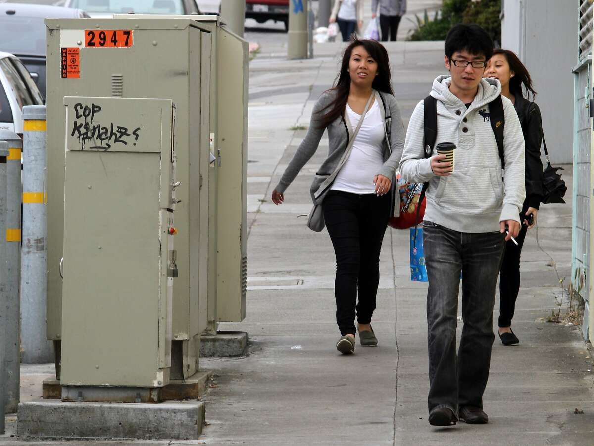 Pedestrians pass by a line of utility boxes lines Taraval St. at 40th Ave. in the Sunset.