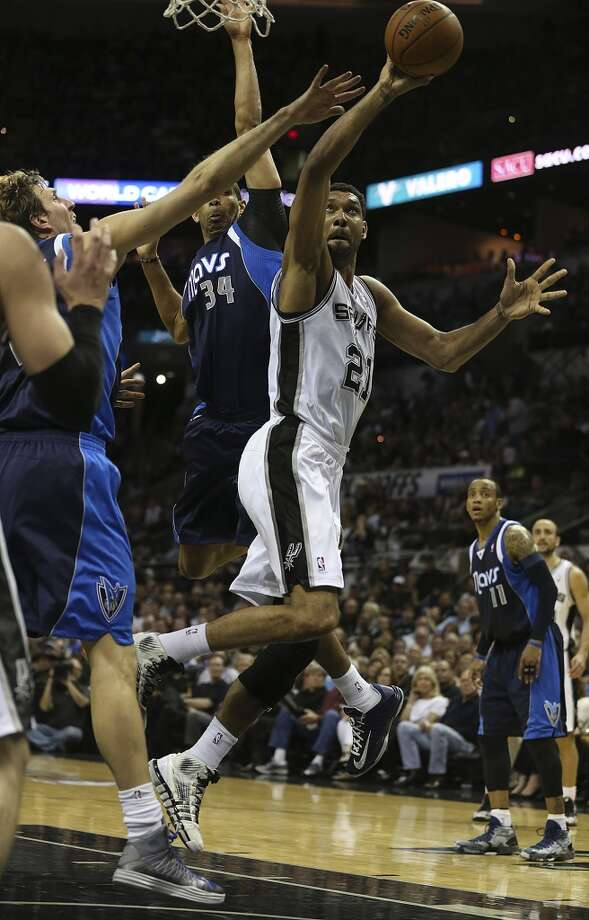 San Antonio Spurs' Tim Duncan shoots between Dallas Mavericks' Dirk Nowitzki, left, and Brandan Wright during the first half of game two in the first round of the Western Conference Playoffs at the AT&T Center, Wednesday, April 23, 2014. Photo: Jerry Lara, San Antonio Express-News