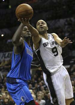 San Antonio Spurs' Tony Parker drives for two around Dallas Mavericks' Samuel Dalembert during the first half of game one in the first round of the Western Conference Playoffs at the AT&T Center, Sunday, April 20, 2014. Photo: Jerry Lara, San Antonio Express-News