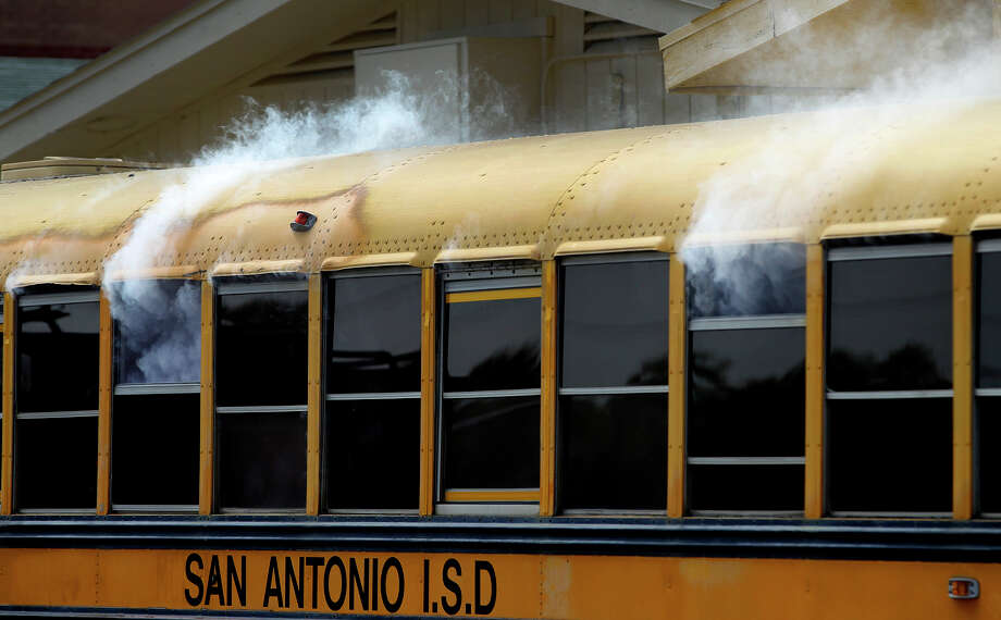 Smoke flows out of a school bus as students and officials take part Thursday May 1, 2014 in a city-supported mass casualty exercise at Edison High School. An Air Life helicopter landing took place as well as simulated explosions and a mock legal hearing. Nearly 200 students, staff, city police, fire and rescue personnel worked together to assist mock victims played by student actors. Photo: JOHN DAVENPORT, San Antonio Express-News / ©San Antonio Express-News/John Davenport