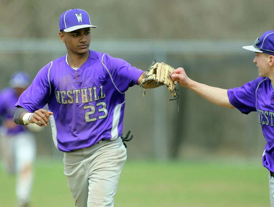 Westhill High School shortstop (#23) Ronald Jackson gets a high five from a teammate following a 5-4 win over Ridgefield High School on Monday, April 14, 2014 in Stamford, Conn. Photo: J. Gregory Raymond / Stamford Advocate Freelance;  © J. Gregory Raymond