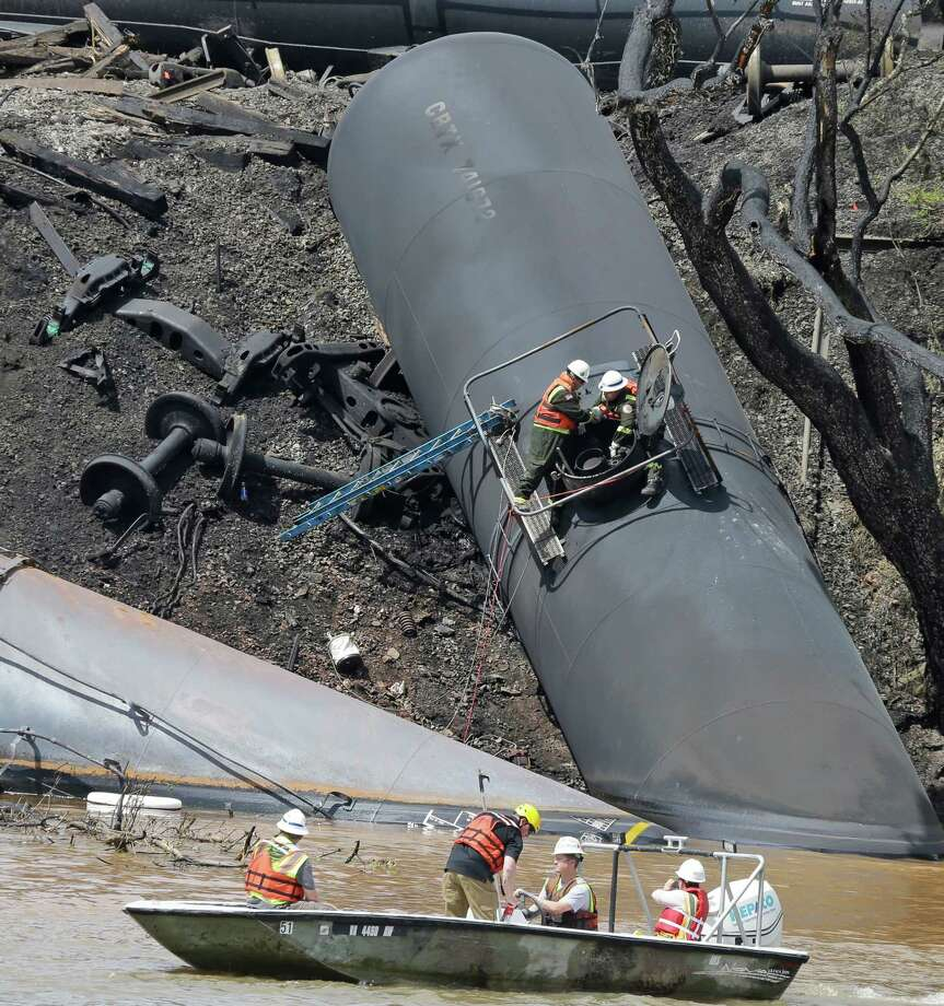 Workers on Thursday remove damaged tanker cars, which were carrying crude oil, that derailed and caught fire along the James River in Lynchburg, Va. Photo: Steve Helber, STF / AP