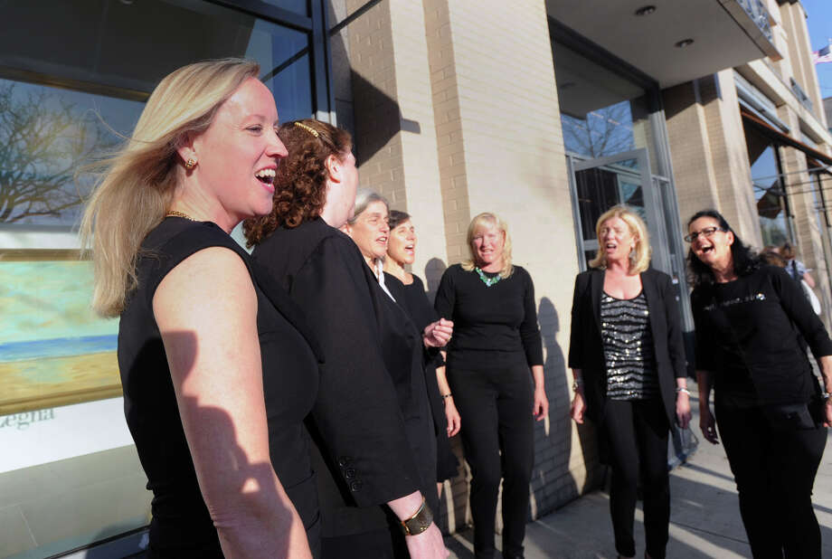 At left, Debbie Hires of the Grace Notes, a twelve-member women's a cappella group from Greenwich, leads the singing during a performance by the group at the Greenwich Arts Council's annual Art to the Avenue event on Greenwich Avenue, Thursday night, May 1, 2014. More than 150 artists will display artworks at local stores and businesses through May 26. All art is for sale. A portion of sales is tax deductible and benefits the Greenwich Arts Council. For a map of artists and their locations, visit www.greenwich arts.org Photo: Bob Luckey / Greenwich Time