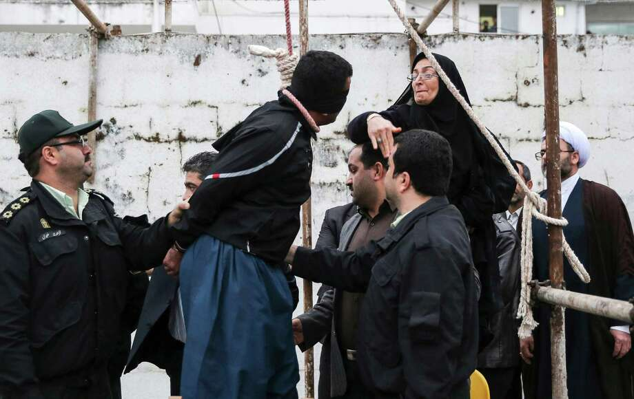 Before removing the noose from his neck, Samereh Alinejad, right, slapped the weeping and blindfolded man, Bilal Gheisari, who had murdered her son. Photo: Arash Khamoushi, STR / Iranian Students News Agency, IS