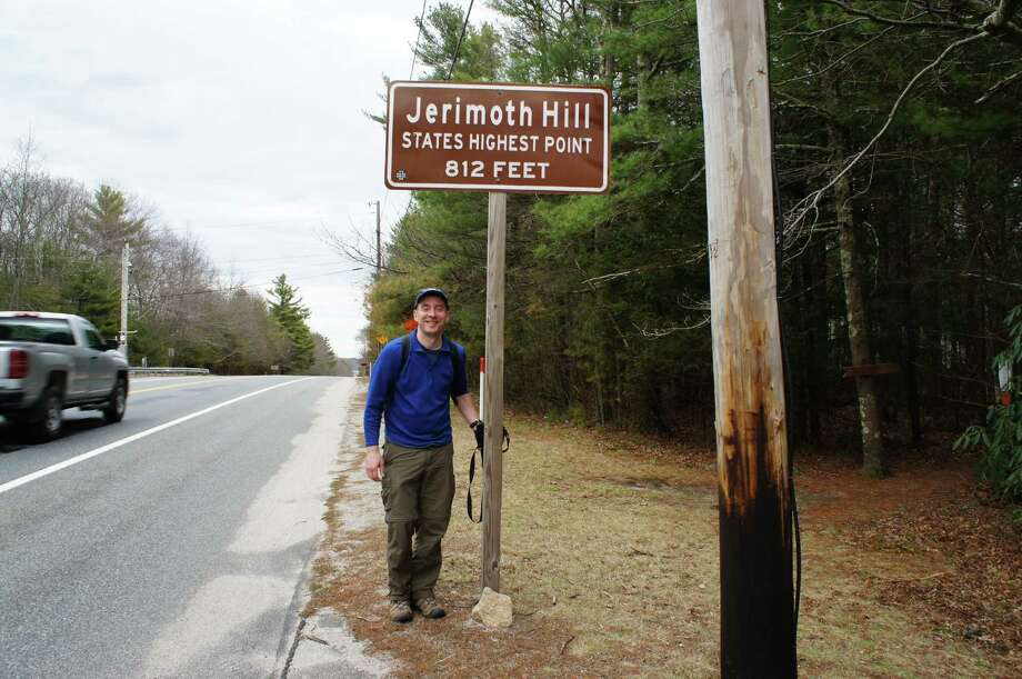 Photo by Gillian Scott. Herb Terns stands next to a sign marking the trail to Jerimoth Hill on Route 101 in Rhode Island.